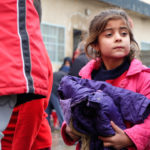 Iraqi Christian child carrying new coat provided by ICC.