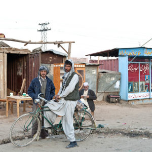 Kabul, Afghanistan - November 18, 2008: An Afghan Man on a bicycle talks to his friend on the street near Darulaman palace