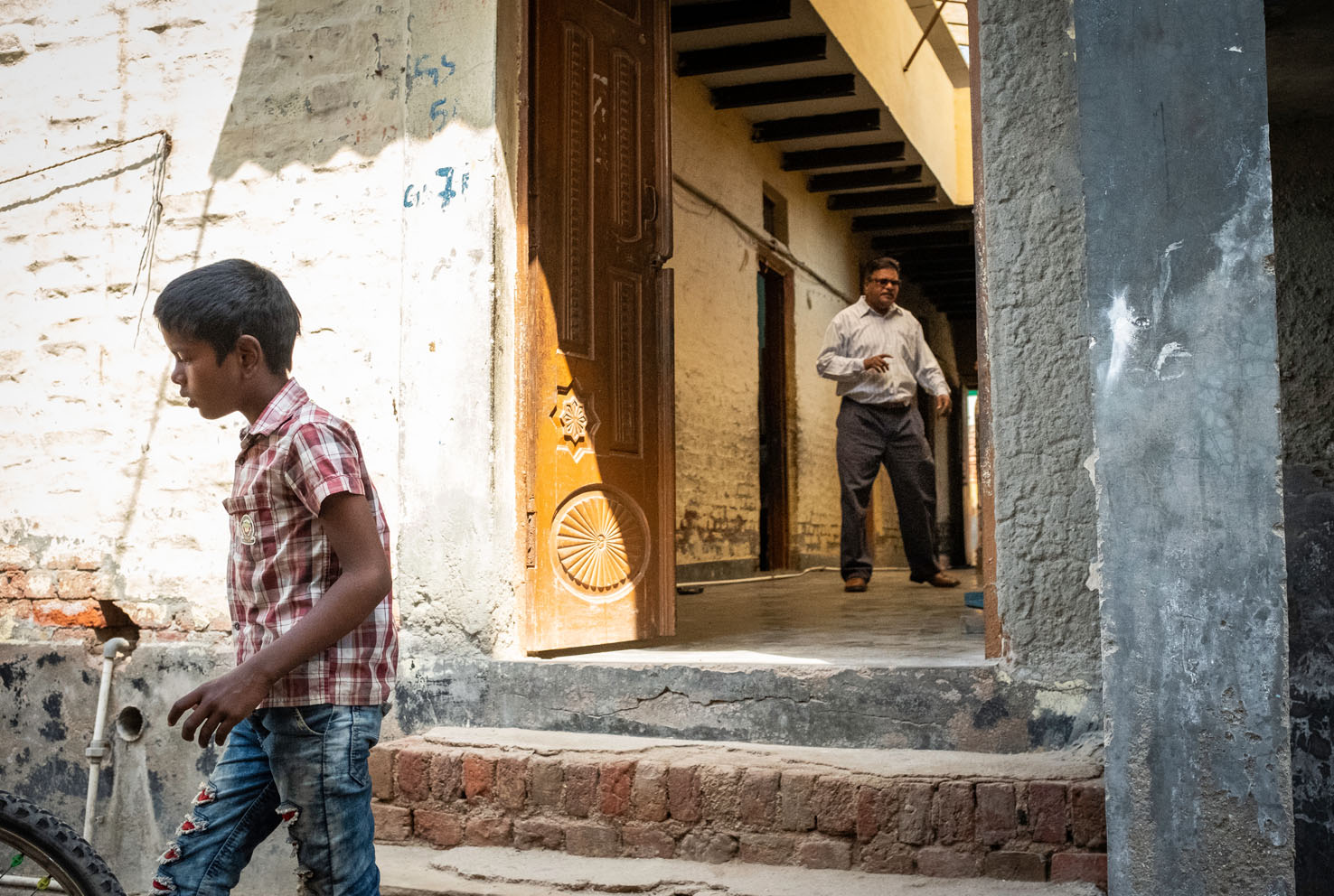 A child exits a former Compassion International school site in New Delhi, India. In 2017, Indian Prime Minister Narendra Modi's Bharatiya Janata Party declared that Christian Non-Governmental Organizations operating within India could no longer receive funding from outside the country. Compassion International, a major provider of education and orphan care, was forced to cease its operations, leaving thousands of children without the provisions the needed to survive. Non-Profit organization Genesis of Hope has managed to maintain several former C.I. school sites, but must fight constant heavy financial challenges to move forward for the children. New Delhi, India. 2018. Photo: John Fredricks