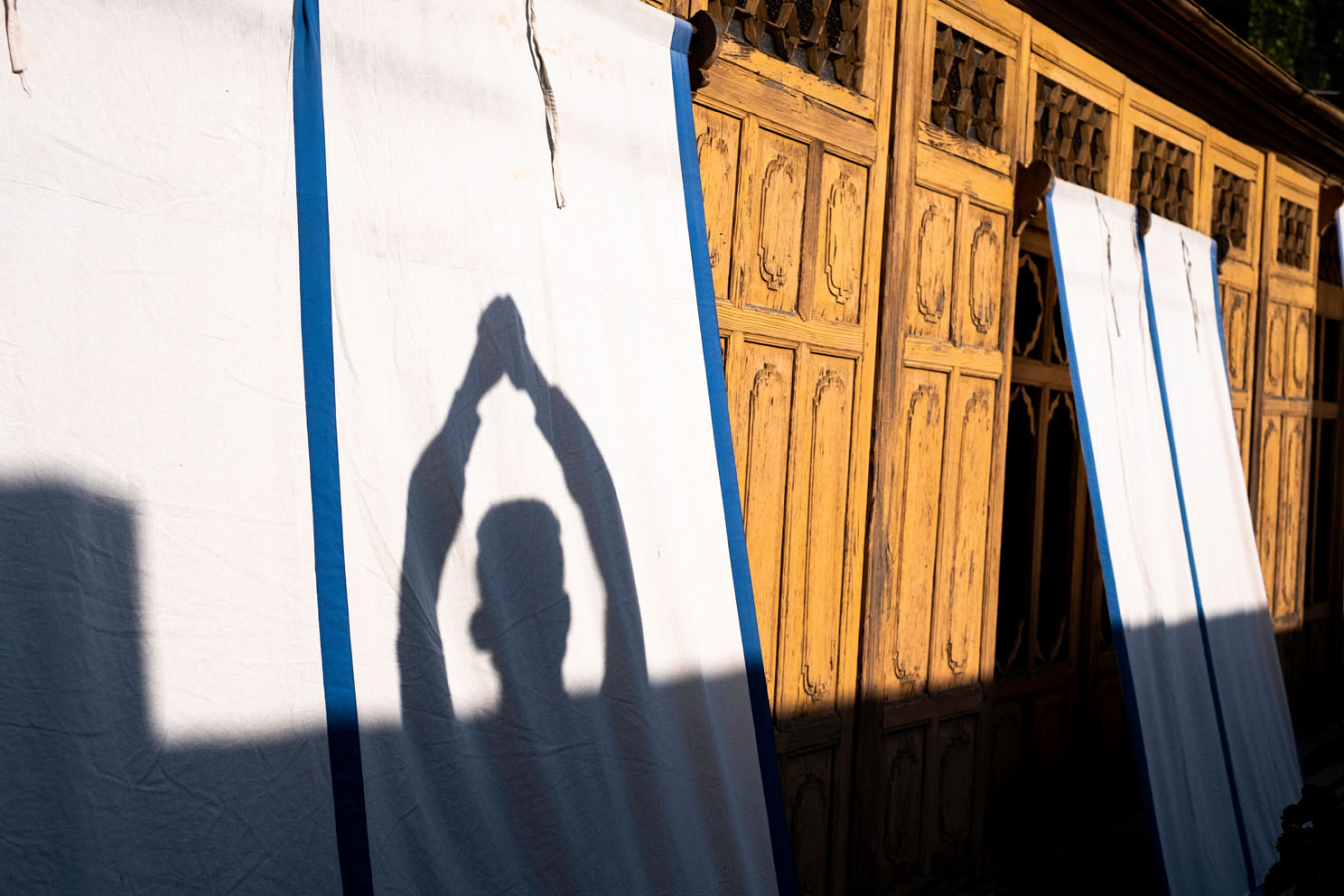 A teenaged Christian boy in Srinagar, India folds his hands in prayer in the afternoon sun. In the 99.5% Muslim state of Kashmir, he stated that all of his friends were devout Muslims, and that Christians in the area must meet in secret to avoid death and arrest by the religious police. (Name and identity has been withheld for the subject's safety). Srinagar, Kashmir, India. 2018. Photo: John Fredricks