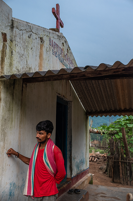 A man leans against the wall of a church that was rebuilt after being destroyed by Hindu nationalists during the 2008 Kandhamal riots. Kandhamal, Odisha, India. 2018. Photo: John Fredricks