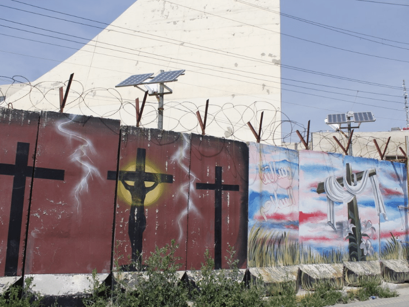 "A bordered fence now posted to prevent any future attacks by extremists on Our Lady of Salvation Church. The fence is decorated with Christian symbols, and the phrase ""Risalatuna Alsalam"" is inscribed on one of the posts, which translates to ""Our Message is Peace."""